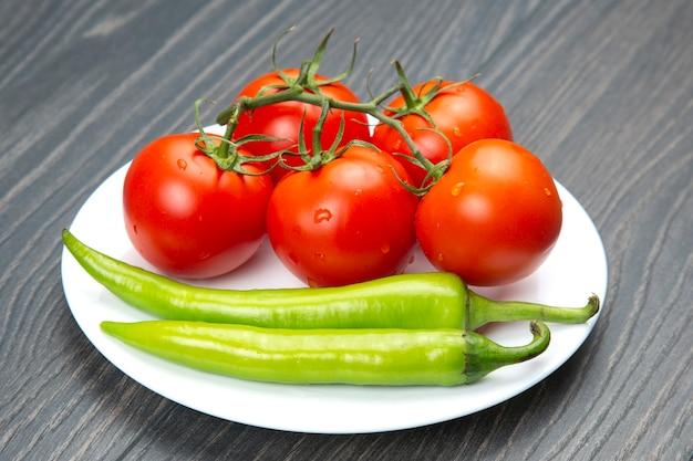 Rote tomaten und grüne peperoni auf einem küchenbrett