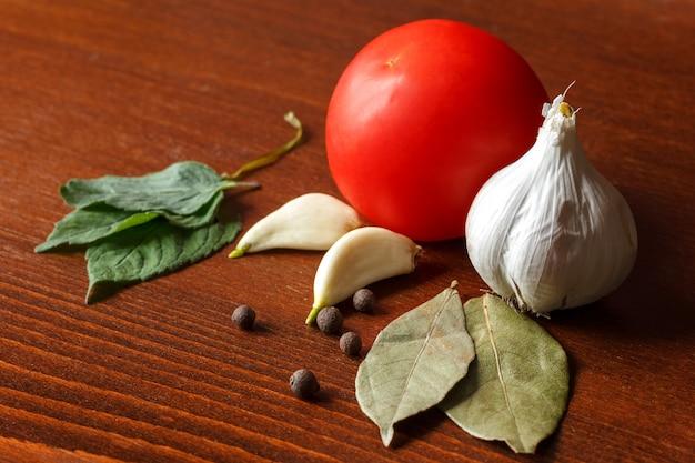 Rote tomaten und knoblauch mit gewürzen liegen auf dem tisch.