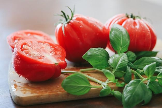 Rote tomaten und minzblätter auf einem holzbrett