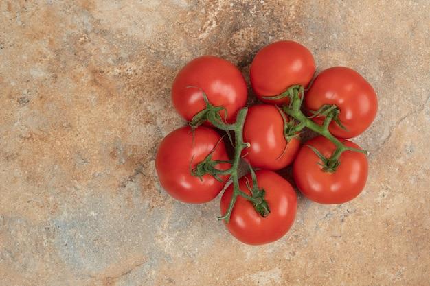 Rote tomatenkirsche auf einem zweig auf marmoroberfläche