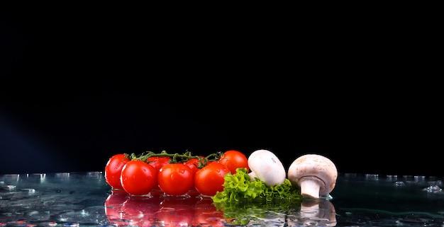 Rote tomatenkirsche, pilze und grüner frischer salat mit wassertropfen