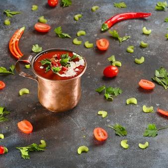 Rote tomatensuppe in der kupfernen schale auf dunkelheit.