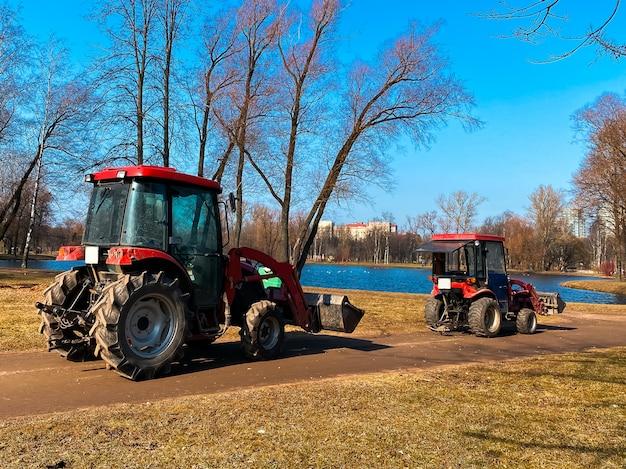 Rote traktoren-lastwagen im frühlingsstadtpark. reinigung. früher frühling. funktioniert. sonniger frühlingstag.