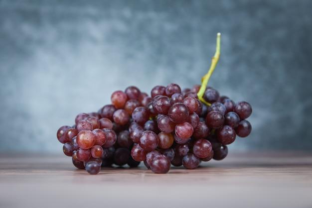 Rote traube auf holztisch, saftige frucht der weintraube auf hellem und dunklem hintergrund