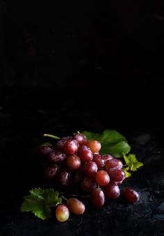 Rote trauben auf einer silbernen schale auf einem dunklen hintergrund