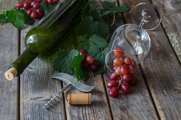 Rote trauben, eine flasche wein, ein glas, ein korkenzieher und ein korken wein