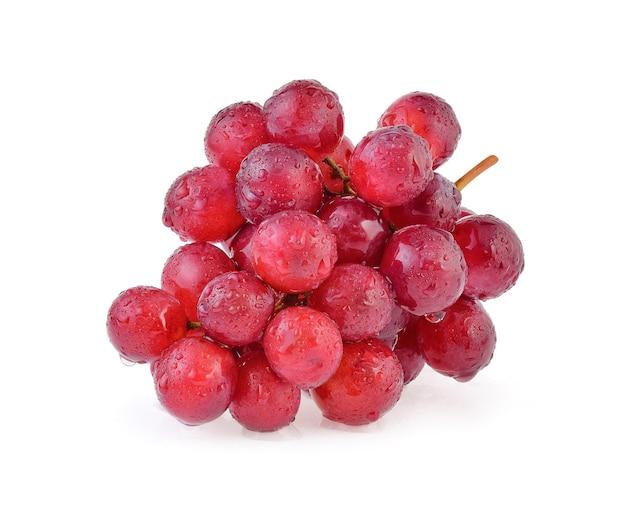 Rote trauben mit wassertropfen auf weißem hintergrund.