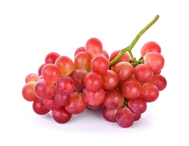 Rote trauben mit wassertropfen auf weißem hintergrund