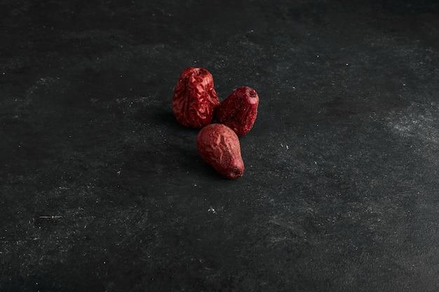 Rote trockene datteln isoliert auf schwarzer oberfläche.