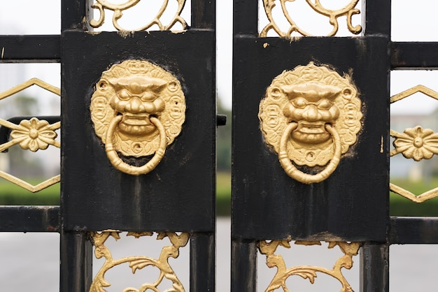 Rote tür der alten architekturtür des traditionellen chinesen und goldener löwe.
