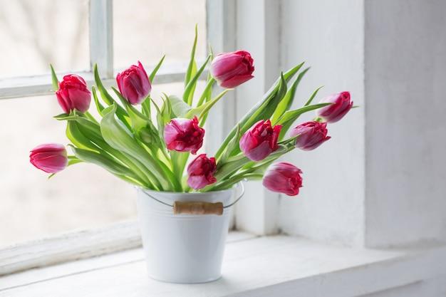 Rote tulpen auf alter weißer fensterbank