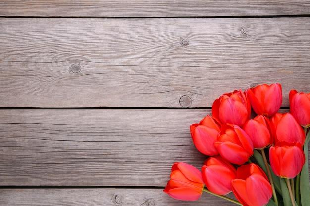 Rote tulpen auf einem grauen hölzernen.