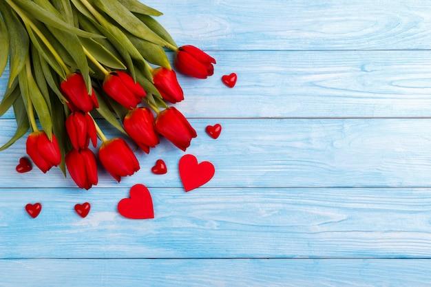 Rote tulpen auf holztisch