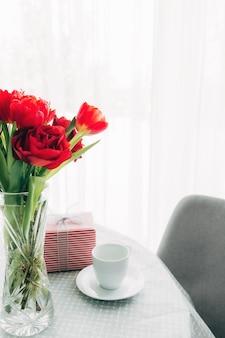 Rote tulpen bouquete auf tisch, weiße kaffeetasse