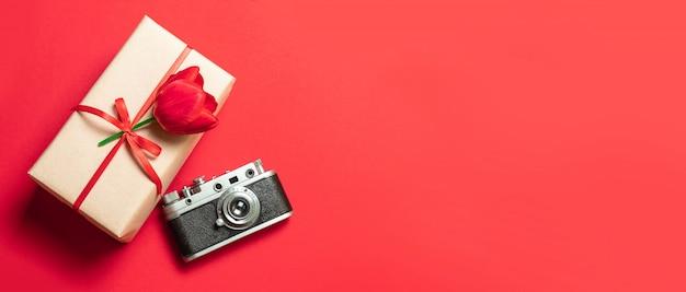 Rote tulpen, geschenkbox und kamera auf rotem hintergrund. flache lage, draufsicht, kopienraum