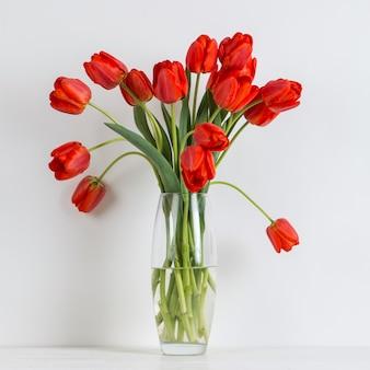 Rote tulpen in einer vase auf dem tisch auf weiß