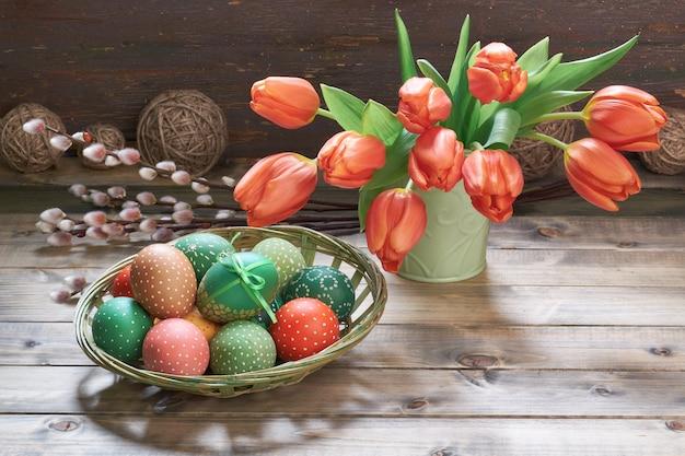 Rote tulpen, ostereier und frühjahrdekorationen auf rustikalem holz