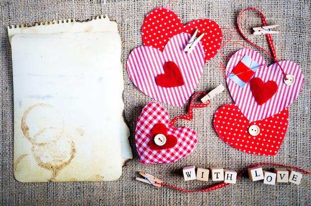 Rote tupfen-textilherzen auf leinwand. freiraum für ihren text.