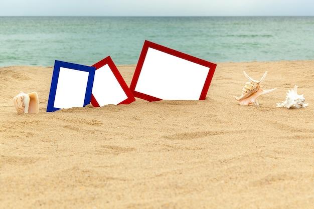 Rote und blaue bilderrahmen mit meeressenken auf dem sand in der nähe des meeres
