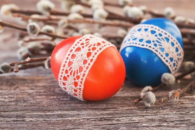 Rote und blaue ostereier verziert mit spitze auf hölzernem hintergrund. selektiver fokus