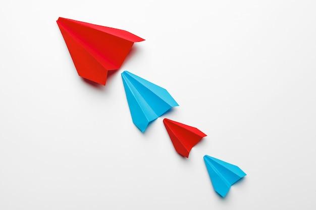 Rote und blaue papierflugzeuge auf weiß