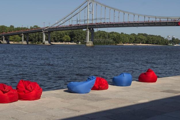 Rote und blaue strandbohnensäcke am flussufer