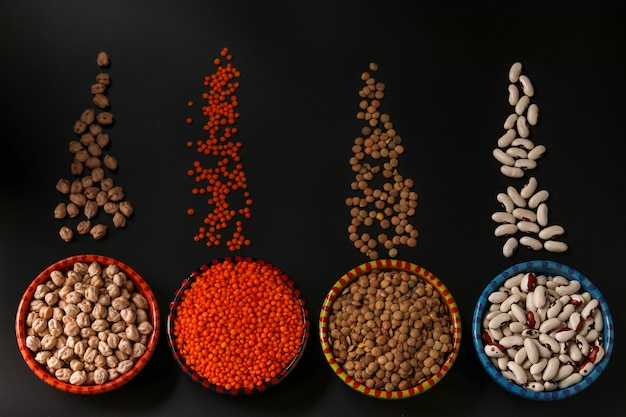 Rote und braune linsen, kichererbsen und weiße bohnen sind hülsenfrüchte, die viel eiweiß enthalten. sie befinden sich auf einem dunklen hintergrund in schalen, horizontaler ausrichtung, draufsicht
