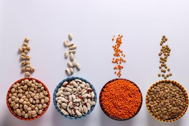 Rote und braune linsen, kichererbsen und weiße bohnen sind hülsenfrüchte, die viel protein enthalten, auf weißem hintergrund in schalen, horizontale ausrichtung, draufsicht