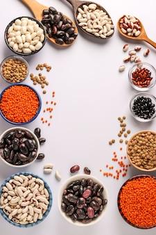 Rote und braune linsen, schwarze, braune und weiße bohnen sind hülsenfrüchte, die viel protein enthalten. sie befinden sich in schalen auf weißem hintergrund