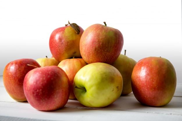 Rote und gelbe äpfel auf weißem holztisch
