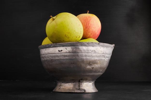Rote und gelbe äpfel in einer metallischen tasse.