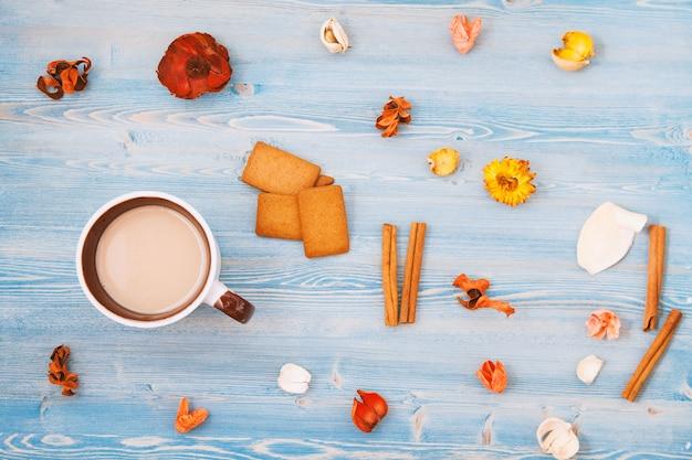 Rote und gelbe blumen, ingwerkekse und ein tasse kaffee auf einem blauen hölzernen