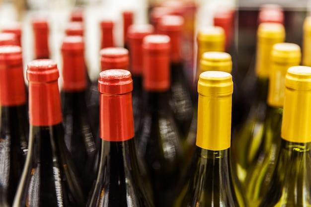 Rote und gelbe flaschen wein im shop. vorbereitung auf die feier