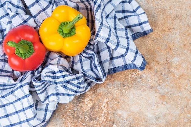 Rote und gelbe frische paprika auf einer tischdecke.