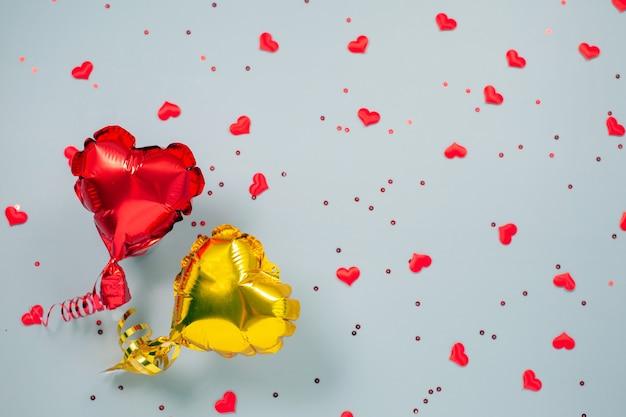 Rote und gelbe luftballons aus herzförmiger folie auf festlich.