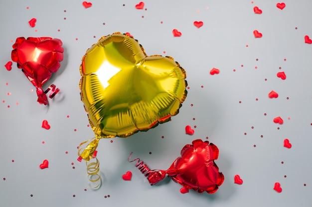 Rote und gelbe luftballons aus herzförmiger folie