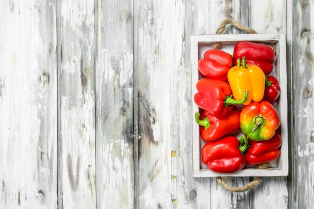 Rote und gelbe paprika auf tablett. auf hölzernem hintergrund