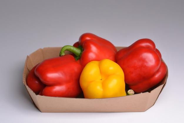 Rote und gelbe paprika in einem papierbehälter