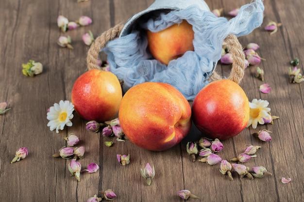 Rote und gelbe pfirsiche auf blauem metallischem eimer auf tuch.