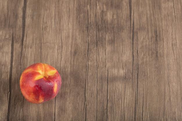 Rote und gelbe pfirsiche auf einem holzdeck isoliert.