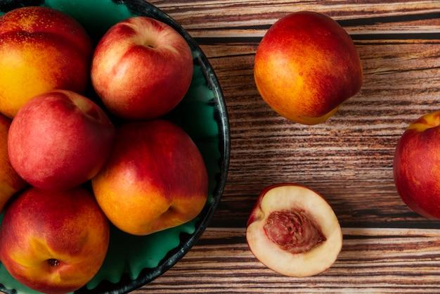 Rote und gelbe pfirsiche in einer grünen platte