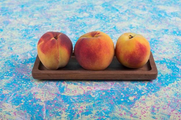 Rote und gelbe pfirsiche in einer holzplatte