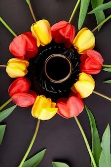 Rote und gelbe tulpen und tasse kaffee des runden kreises