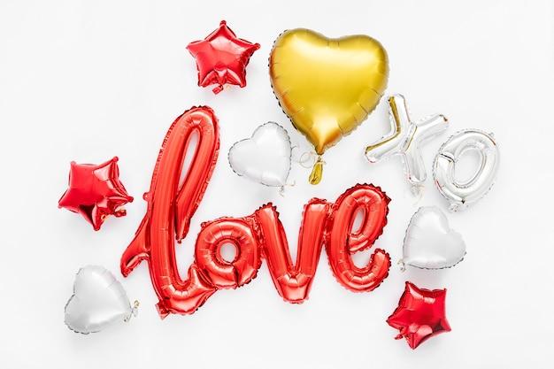Rote und goldene folienballons in form des wortes
