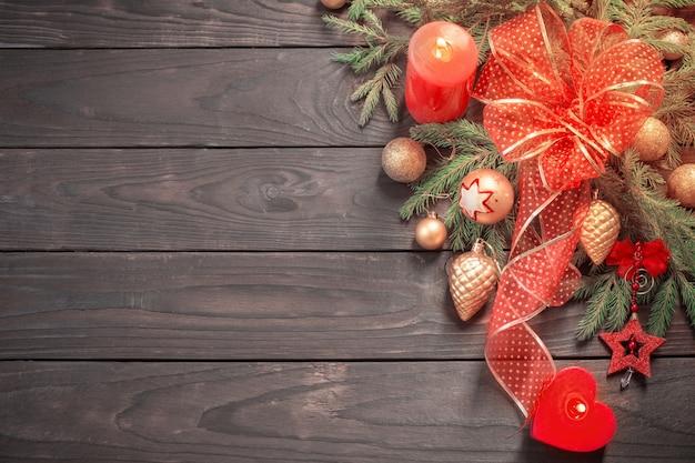 Rote und goldene weihnachtsdekoration mit brennender kerze auf hölzernem hintergrund