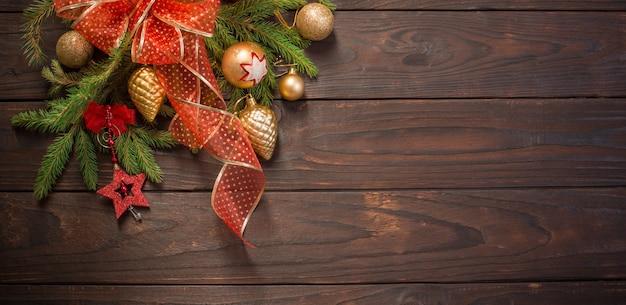 Rote und goldene weihnachtsdekoration mit brennender kerze auf holzoberfläche