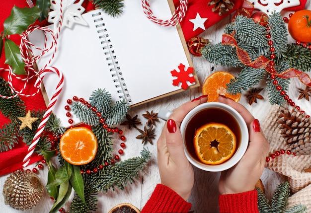 Rote und goldene weihnachtskomposition mit notizbuch und teetasse