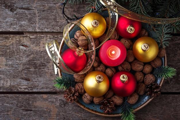 Rote und goldene weihnachtskugeln auf platte. selektiver fokus