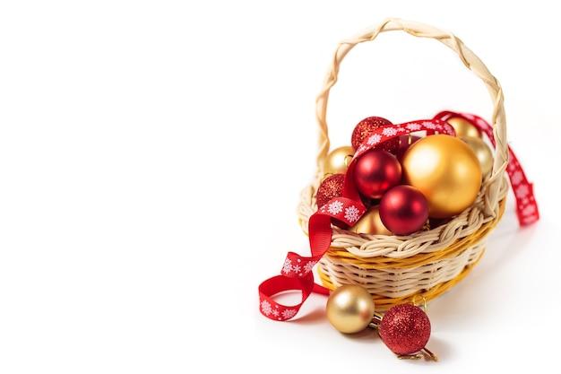 Rote und goldene weihnachtskugeln in einem kleinen korb
