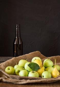Rote und grüne äpfel. äpfel in schüssel gelbe birnen apfelwein. fruchtessig apfelwein